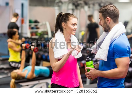 Fit couple chatting in weights room at the gym - stock photo