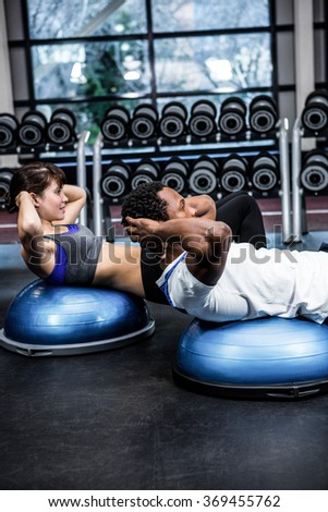 Fit couple doing bosu ball exercises at gym - stock photo