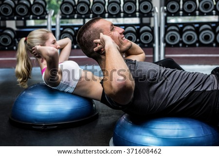 Fit couple doing sit ups on bosu ball at gym - stock photo