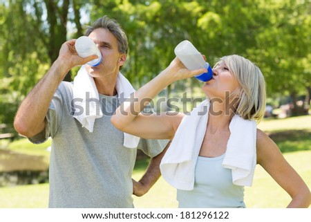 Fit couple drinking water from bottles after workout in the park - stock photo