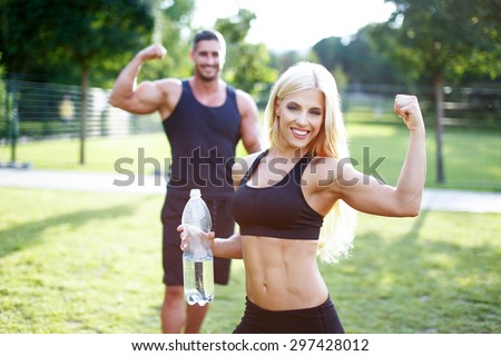Fit couple in nature with bottle of water, blonde woman showing biceps, healthy lifestyle - stock photo
