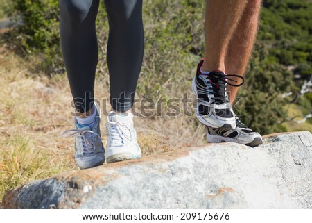 Fit couple jogging up mountain trail on a sunny day