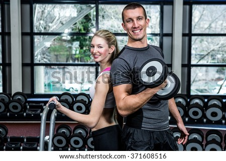 Fit couple lifting dumbbells back to back at gym - stock photo
