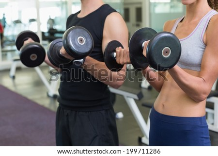 Fit couple lifting dumbbells together at the gym