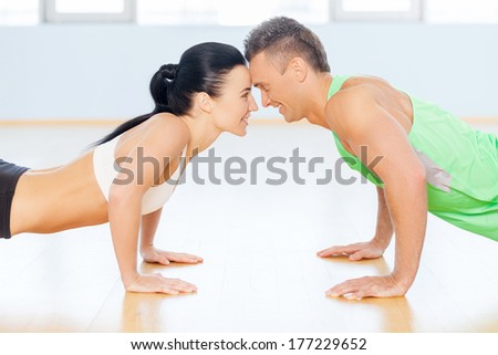 Fit couple. Man and woman doing push-up looking to each other - stock photo
