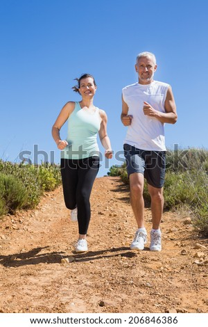 Fit couple running down mountain trail on a sunny day