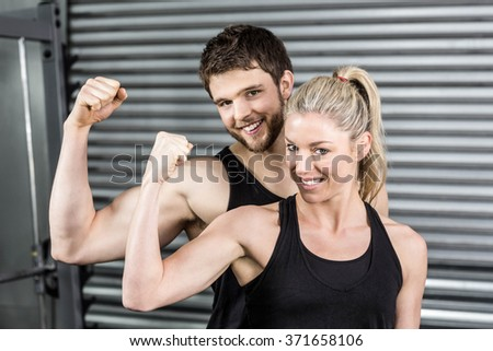 Fit couple showing muscular arms at crossfit gym - stock photo