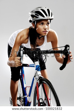 Fit cyclist woman on road racing bicycle isolated in studio with dramatic lighting. Riding bike as if in a race. - stock photo