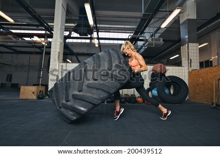 Fit female athlete working out with a huge tire, turning and flipping in the gym. Crossfit woman exercising with big tire. - stock photo