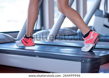 fit female legs on a treadmill at the gym