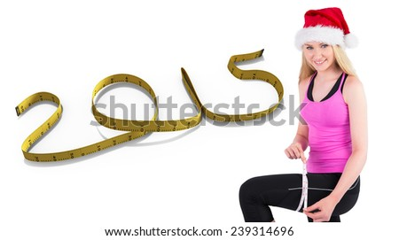 Fit festive young blonde measuring her thigh against 2015 in tape - stock photo
