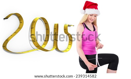 Fit festive young blonde measuring her thigh against 2015 tape - stock photo