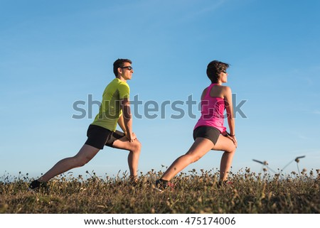 Fit fitness couple doing stretching exercises during flexibility workout routine outdoor on direct sunlight on grass before trail running training.
