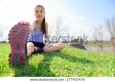 Fit fitness woman doing stretching exercises outdoors on grass. Girl doing hamstring leg stretching exercise and stretches. Female sports model exercising outdoor in summer. Beautiful Asian girl. - stock photo