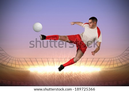 Fit football player playing and kicking against large football stadium with spotlights at sunrise