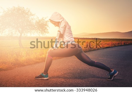 Fit girl stretching outdoors before running training - stock photo