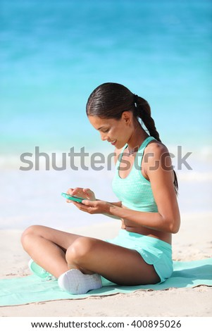 Fit girl using fitness app on phone during travel holidays on beach texting or posting on social media online. Healthy sporty Asian woman living a happy active life exercising on towel. - stock photo