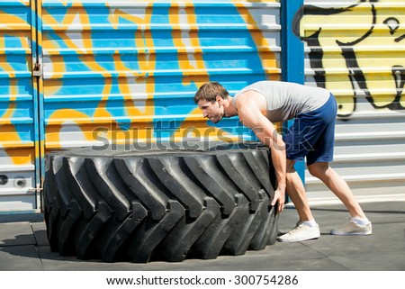 Fit girl with giant truck tire doing cross style workout turning tire over.