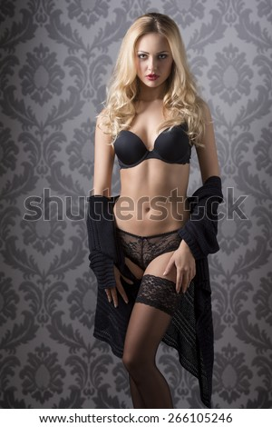 fit girl with long blonde hair wearing dark lingerie and sexy lace stockings, perfect body looking in camera  - stock photo