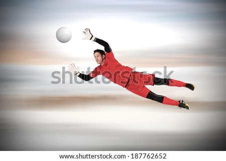 Fit goal keeper jumping up against grey blurred background - stock photo