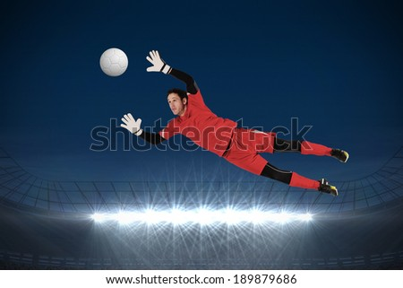 Fit goal keeper jumping up against large football stadium with spotlights under dark sky - stock photo