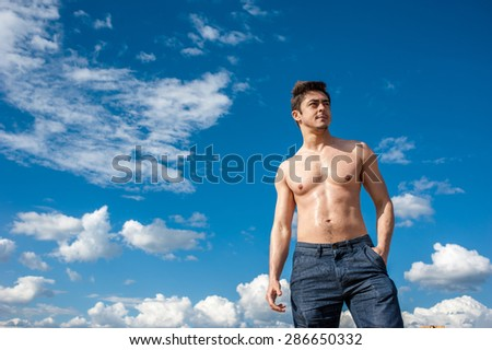 Fit handsome healthy athletic young man with bare torso enjoying life under scenic blue sky on sunny day. Concept of recreation, healthy lifestyle and well being.