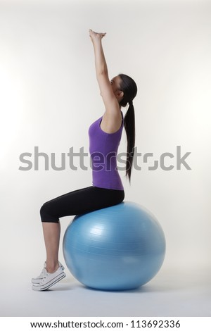 fit looking young woman doing stretching exercises on a gym ball