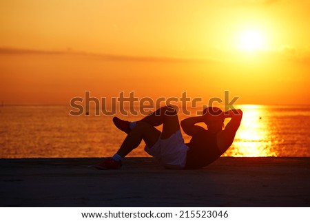 Fit male athlete working out cross training on colorful sunrise background, silhouette of handsome muscular man doing sit-ups, sportsman doing crunch abdominals exercise, healthy lifestyle concept - stock photo