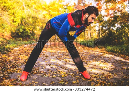 Fit male fitness athlete model training outdoor in fall. Stretching his legs. Selective focus