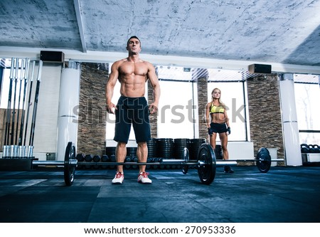 Fit man and woman workout with barbell at gym - stock photo