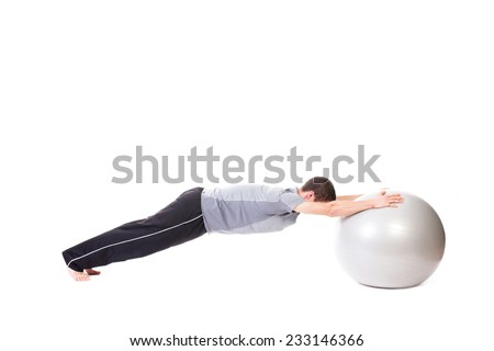 Fit man doing push-up exercises using a white fitness ball - isolated on white.