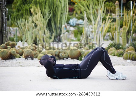 Fit man doing sit ups exercise before going for a run outdoors, sporty black man training outside - stock photo