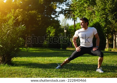 Fit man doing stretching exercises outdoors, young male sportsman stretching and preparing to run, attractive adult runner stretching the legs standing on grass in the park, sports fitness concept - stock photo