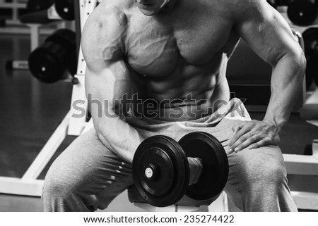 Fit man exercising at the gym on a machine.Man at the gym. Man makes exercises. Sport, power, dumbbells, tension, exercise - the concept of a healthy lifestyle. Article about fitness and sports.