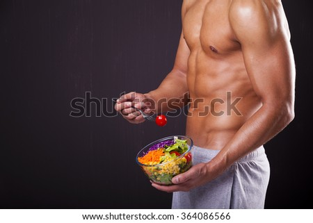 Fit man holding a bowl of fresh salad on grunge background - stock photo