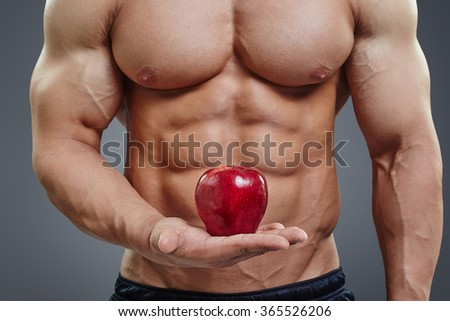 Fit man holding a fresh red apple on grey background. Healthy food abstract concept. Shirtless bodybuilder with perfect six pack abs healthy diet concept. - stock photo