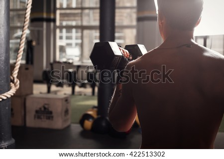 Fit man in gym working out - stock photo