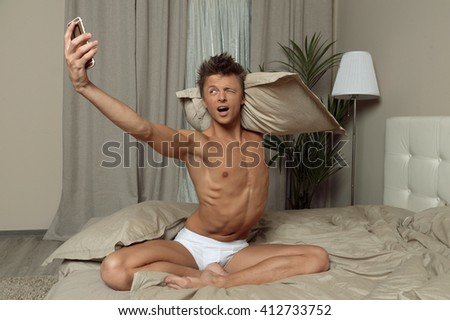 Fit man in underwear take selfie on bed  in bedroom - stock photo