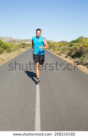 Fit man jogging on the open road on a sunny day - stock photo