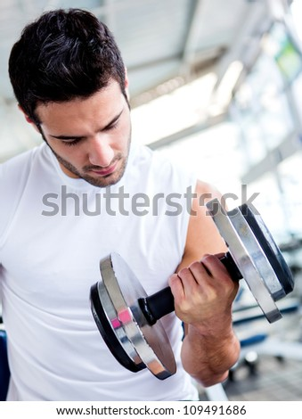 Fit man lifting weights at the gym - stock photo