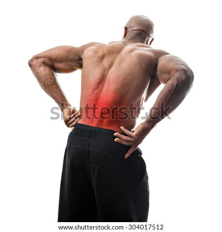 Fit man or athlete reaching for his lower back in pain with the painful area highlighted in red.  - stock photo