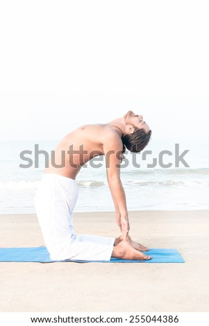 Fit man performing yoga asana on the beach - stock photo