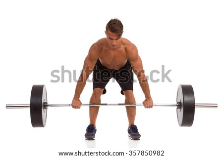 Fit Man Picking Up A Barbell. Full length studio shot isolated on white. - stock photo