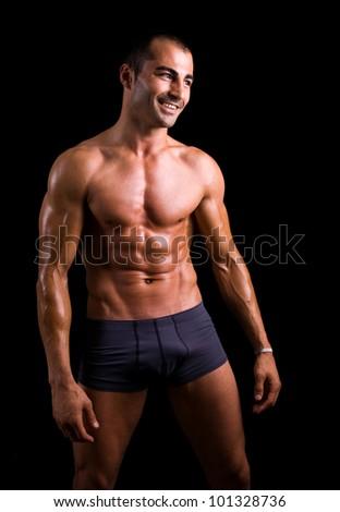 Fit man posing on black background - stock photo