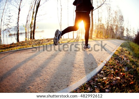 Fit man running in park during autumn, winter sunrise