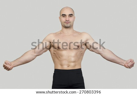 Fit man spreading arms showing his body. Strong bodybuilder man with perfect abs, shoulders,biceps, triceps and chest flexing his muscles. - stock photo