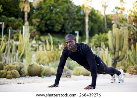 Fit man working out in the park doing push-ups exercise, sporty black man training outdoors - stock photo
