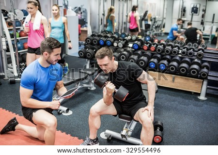 Fit man working out in weights room at the gym - stock photo
