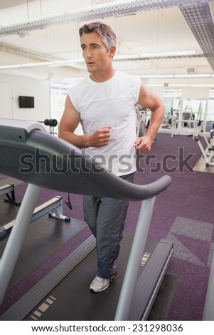 Fit man working out on treadmill at the gym