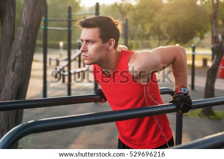 Fit man workout out arms on dips horizontal bars training triceps and biceps doing push ups outdoors.
